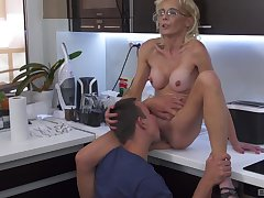 Skinny mature blonde mixes it up with a young fella in the kitchen